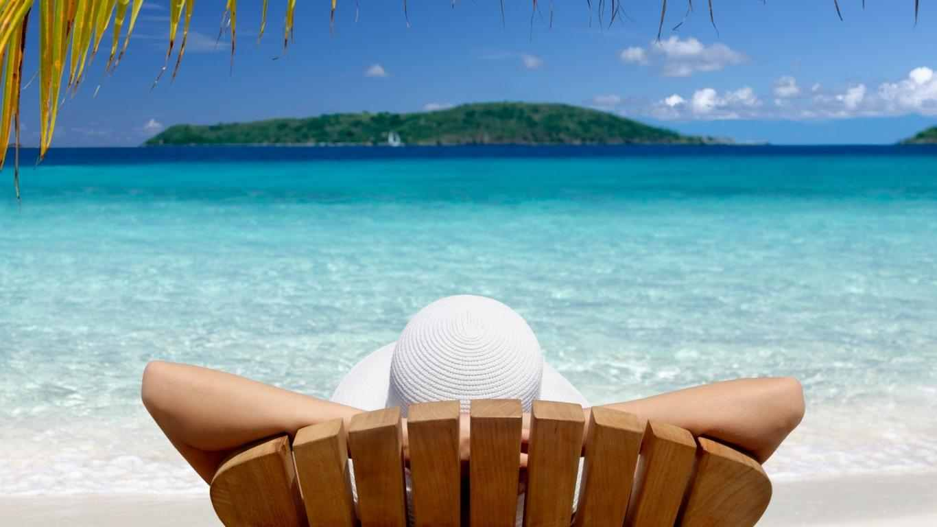 Woman relaxing in wooden chair on beach overlooking blue water.